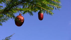 Christmas tree retro decoration. Real Christmas tree branch decorated with old style balls outdoor against blue sky stock video footage