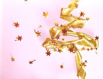 Christmas tree from ribbons. Gold glitter ribbon in shape of Christmas tree on pink background. Copyspace for text, royalty free stock photography