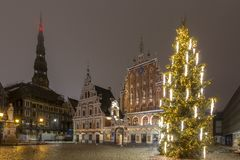 Christmas Tree of Riga, Latvia with illuminated House of Blackheads and St Peter church against the dark blue night sky. Royalty Free Stock Photography