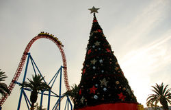 Christmas tree with a roller coaster in the background Royalty Free Stock Images