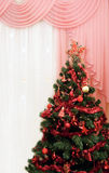 Christmas tree in a room next to window Stock Photo