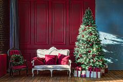 Christmas tree in royal interior. New Year`s Living Room with antique stylish white sofa with luxurious golden accessories. Gifts royalty free stock image
