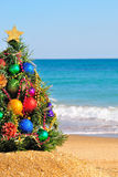 Christmas tree on sand in the beach Royalty Free Stock Photos