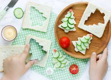 Christmas tree sandwiches, child hand cooking snack for Christma. S holiday top view Stock Photography