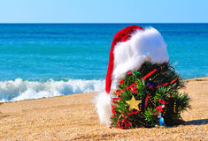 Christmas tree and santa hat on sand on beach Stock Photography