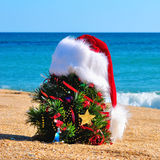 Christmas tree and santa hat on the sand in the beach Stock Photo