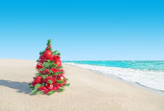 Christmas tree at sea beach. New Years vacation concept. Stock Photo