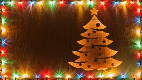 Christmas tree shape cut in wooden board framed by xmas lights royalty free stock image