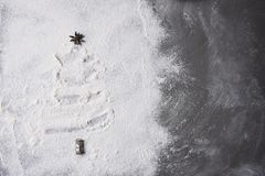 Christmas tree shape in flour spread out on a baking sheet. Tree topper is a star anise pod Royalty Free Stock Photos