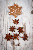 Christmas tree shape made of anise and decorated gingerbread on old wooden background Royalty Free Stock Photography