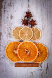 Christmas tree shape made of dried orange, lemon and anise on old wooden background Royalty Free Stock Photos