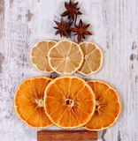 Christmas tree shape made of dried orange, lemon and anise on old wooden background Royalty Free Stock Images