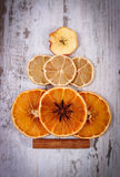 Christmas tree shape made of dried orange, lemon and apple on old wooden background Stock Images