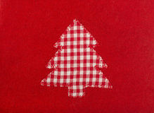 Christmas tree shape on red wool background. Stock Photos