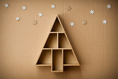 Christmas tree shaped gift box and decorations, on cardboard background Royalty Free Stock Photography