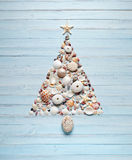 Tropical Christmas Tree Shells Background. A christmas tree made of shells on a blue painted background Stock Photos