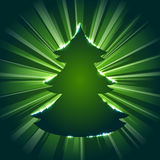Christmas tree silhouette against a starburst. Dark green tree silhouette with sparkles and a starburst background. Graphics are grouped and in several layers Royalty Free Stock Photography