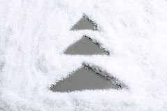 Christmas tree silhouette in snow on color background. Top view royalty free stock photography
