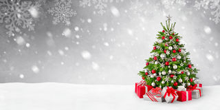 Christmas tree and snow background. Gorgeous elegant Christmas tree with gifts in red and silver on a panoramic snow background