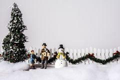 Christmas Tree and Snow Man. A snow covered Christmas scene with father and daughter with puppy between decorated tree and snow man white picket fence with Stock Photos