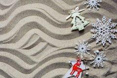Christmas tree and snowflakes lie on the sea sand.  stock photo