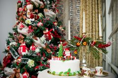 Christmas tree and a special cake. Details from a Christmas tree with special ornaments and a table with a Christmas cake with mini figurines royalty free stock images