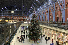 Christmas tree in St Pancras Station, London. Christmas tree, decorations and people in concourse at St Pancras station in London, England royalty free stock images