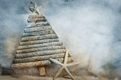 Christmas tree with starfish. A wooden Christmas tree with starfish decoration on a textured surface in blue and brown Stock Photography