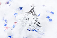 Christmas tree and stars. Christmas tree and star shaped confetti on snow stock photography