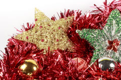 Christmas tree stars and baubles of different types over a red garland Stock Image