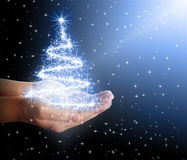 Christmas tree of stars and lights in their hands. On black background Stock Photography