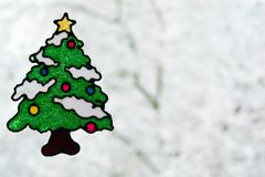 Christmas tree stickers for window. Behind the Christmas tree is a tree covered with snow stock photos