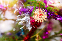 Christmas tree straw toy. Decoration in shape of snowflake hanging on tree branch. Festive New year blurred background with bokeh Stock Image