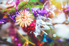 Christmas tree straw toy. Decoration in shape of snowflake hanging on tree branch. Festive New year blurred background with bokeh Royalty Free Stock Photo