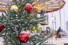 Christmas tree on the street is decorated with colorful toys on the background of the carousel stock photography