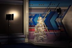 Christmas tree in the Studio video, lighting on both sides. White Christmas tree with gold toys. Christmas office decoration. Christmas tree in Studio video stock image