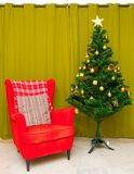 A Christmas Tree In The Suburbs. A Christmas tree in front of an olive curtain filled with colourful ornaments in a suburban apartment home Royalty Free Stock Photography