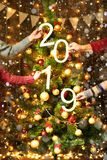Christmas tree with 2019 text and people hands, new year decoration and lights on wooden background, holiday concept backdrop royalty free stock photography