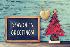 Christmas tree and text seasons greetings in a chalkboard. A chalkboard with the text seasons greetings written in it and a rustic wooden christmas tree and a Stock Image
