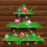 Christmas tree of three wood shelves. Showcases with shadow on brown wooden panel wall background. Advertising holiday plank shelf store. Sale interior Royalty Free Stock Image
