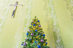 Christmas tree with tinsel and balls and the cross. Christmas tree decorate with tinsel and balls with the stainless cross on the wall Stock Photo
