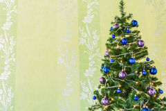 Christmas tree with tinsel and balls. Christmas tree decorate with tinsel and balls against beautiful wall paper Royalty Free Stock Images