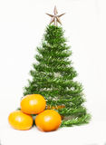 Christmas tree from a tinsel. Toy Christmas tree with three tangerines on a white background Royalty Free Stock Photos