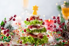 Christmas tree appetizer. Christmas tree from toasted bread, lettuce, ham and cheese. Festive idea for Christmas or New Year dinner royalty free stock photography