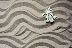 Christmas tree toy in beach sand.  royalty free stock image