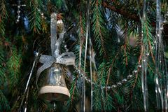 Christmas tree toy bell. Christmas tree toy bell on a green branch. Old Russian toy Royalty Free Stock Images