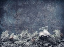 Christmas tree on toy car rides on fir branches on dar blue background, Holiday greeting card with copy space. For your design royalty free stock photography