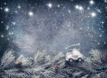 Christmas tree on toy car rides on fir branches on dar blue background with painted snow. Greeting card. With copy space for your design royalty free stock images