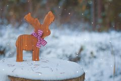 Christmas-tree toy deer with a ribbon on the snow. With a copy-space. royalty free stock photography