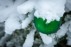 Christmas tree toy green ball hanging under the snow on a branch of fir on the right. Real winter in the garden. Selective focus with amazing snow blur. There royalty free stock photography